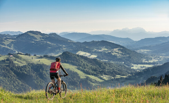 pretty senior woman riding her electric mountain bike on the mountains above Oberstaufen, Allgau Alps, Bavaria Germany