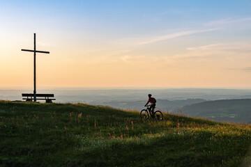 pretty senior woman riding her electric mountain bike in warm dawn sunlight below the summit cross of Salmas hight above Oberstaufen, Allgau Alps, Bavaria Germany