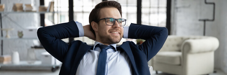 Foto auf Acrylglas Entspannung Horizontal panoramic view of smiling young Caucasian businessman look in distance relax at workplace, happy male employer or boss dreaming thinking in office, business vision, success concept