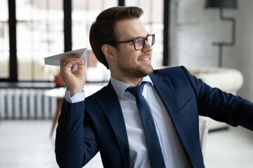 Smiling young Caucasian male employer or CEO have fun throw paper plane at workplace, happy businessman distracted from work, relax entertain in office, entertainment, business project launch concept