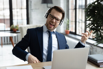 Fototapeta Overjoyed young Caucasian male office employee in suit wear headset listen to rock music at workplace, happy businessman in headphones relax have fun enjoy good quality audio, stress free concept