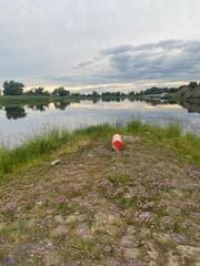 Fototapeta Boje am Ufer eines Flusses am Abend obraz