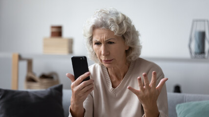 Angry mature woman sit on couch at home feel frustrated by slow internet connection on cellphone,...