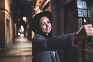 Fotomurales - Traveler female blogger shooting video for vlog social media with digital camera. Smiling woman vlogger taking selfie video on light night city