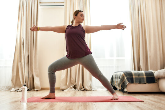 Coolest yoga. Full length shot of young curvy woman in sportswear practicing yoga on a mat at home