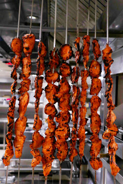 spice marinated chicken cubes ( chicken tikka )skewers cooking in a clay oven known as tandoor