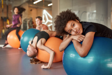 African american teenage boy looking tired while working out with exercise ball in gym. Sport,...