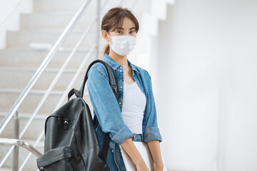 Young student woman wear face mask carry backpack laptop in university