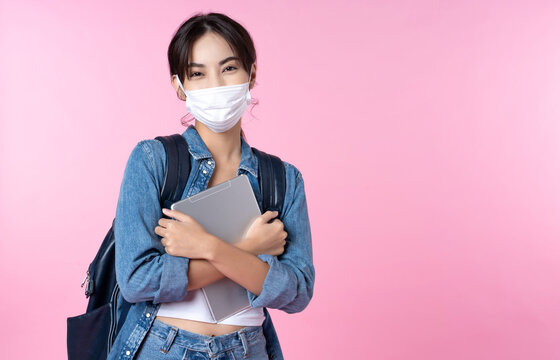 Portrait of young Asian college student wears face mask with laptop
