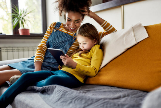 Quality childcare matters. African american woman baby sitter and caucasian cute little girl smiling, using tablet pc, sitting at home. Children education, leisure activities, babysitting concept