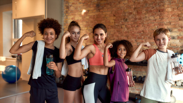 We are strong. Happy female trainer and positive children showing muscles while smiling at camera, standing in gym