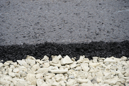 a thin layer of fresh black asphalt on a half-foot of gravel and rubble, stage of road construction, a sandwich
