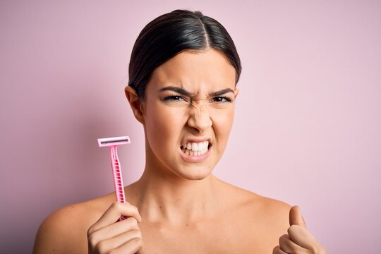 Young beautiful girl using shaver for depilation standing over isolated pink background annoyed and frustrated shouting with anger, crazy and yelling with raised hand, anger concept