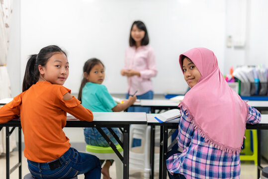 Asian female teacher teaching kid writing lesson and reading book in classroom, Special education during school holidays.