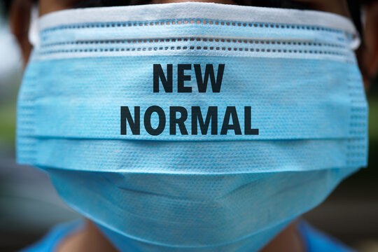 NEW NORMAL word on 3 ply face surgical mask. Life after pandemic concept.