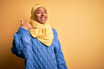 Young African American afro woman wearing muslim hijab over isolated yellow background smiling doing phone gesture with hand and fingers like talking on the telephone. Communicating concepts.