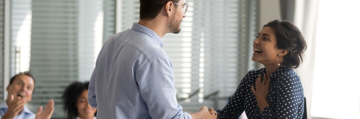 Diverse businesspeople shake hands standing in office. Company boss congratulate indian female...