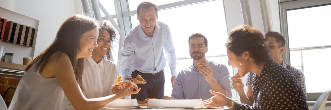 Group of multiethnic colleagues friends gathered together eating pizza talking and laughing during lunch break. Teambuilding, corporate party concept. Horizontal photo banner for website header design