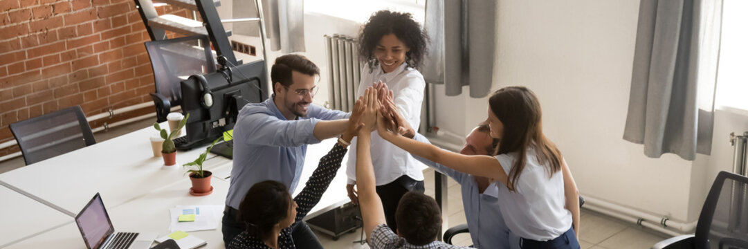 Horizontal photo banner for website header design, above view group of multi ethnic businesspeople colleagues stack palms together giving high five celebrating common success. Team building concept