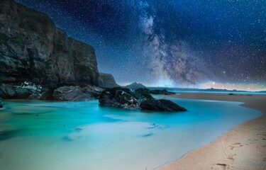 Beach surrounded by the sea and rocks under a bright starry sky at night - perfect for backgrounds
