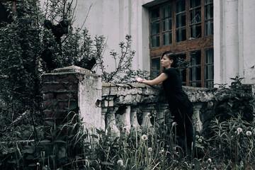 Tuinposter Begraafplaats A girl stands near an old abandoned manor