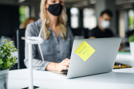 Unrecognizable young woman with face mask back at work in office after lockdown.