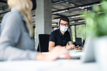 Young people with face masks back at work in office after lockdown, talking.