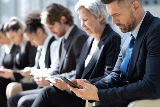 Group of business people with smartphones sitting in a row