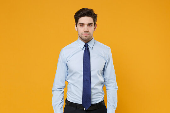 Successful confident young business man in classic blue shirt tie posing isolated on yellow background studio portrait. Achievement career wealth business concept. Mock up copy space. Looking camera.