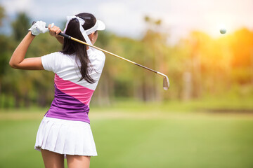 Asian girls are playing golf on a sunny day on the beautiful green golf course.