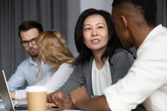 Focus to asian ethnicity middle-aged woman mentor more experienced worker teach African guy millennial intern, diverse staff members sitting in co-working shared room working on common project concept