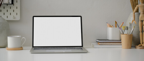 Wall Mural - Minimal worktable with blank screen laptop, cup, painting tools and decorations on white table