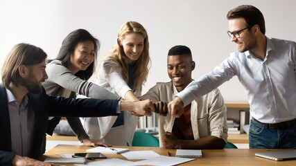 Horizontal image middle-aged and young five multiracial staff members gather in boardroom show unity stacked hands in circle, fists bumping symbol of togetherness common goals business loyalty concept