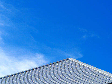 Slate roof and slope with clouds and blue sky background.Tile roof of construction house with blue sky and cloud background