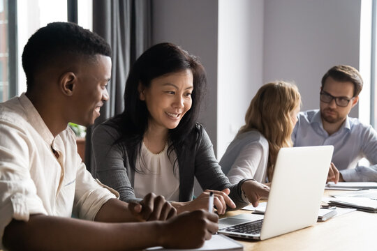 Multi-ethnic affiliates working on task together seated at desk in co-working, mature asian mentor teach new employee african guy, diverse mates having fun using laptop, learn corporate apps concept