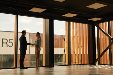 Wide angle view of real estate agent shaking hands with client while standing in empty office building interior lit by sunlight, copy space