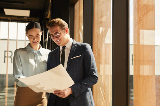 Waist up portrait of smiling rental agent showing floor plans to female client while standing in office building interior lit by sunlight, copy space