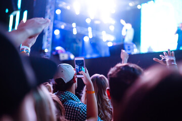 Hand with a smartphone records live music festival, Taking photo of concert stage. Youth, party, vacation concept.