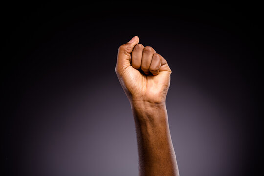 Close up photo of afro american hand raise fists ask support african community stop discrimination isolated over black color background
