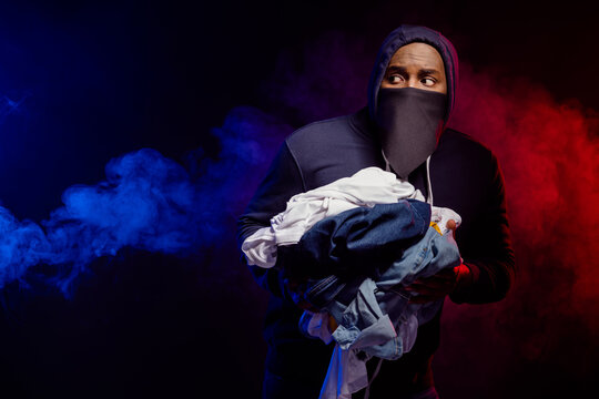Photo of scared afro american guy rob boutique hold fashion wear clothes look copyspace if police chase him isolated over black smoke color background