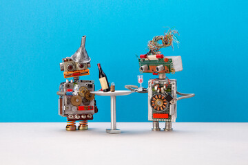 Two robots celebrate system upgrade. Wine booze party concept. Funny toy characters at a simplified restaurant table on blue gray background