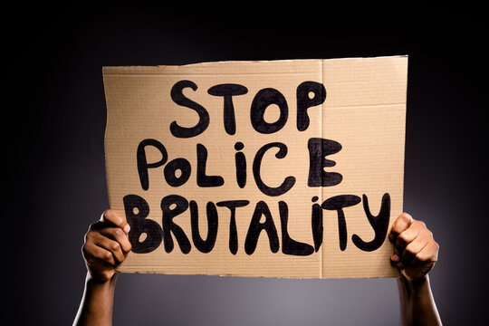 Close up photo of afro american hand hold cardboard banner show stop police brutality message isolated over black color background