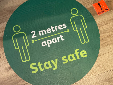 A social distancing sticker on the floor warning people to stay 2 metres apart