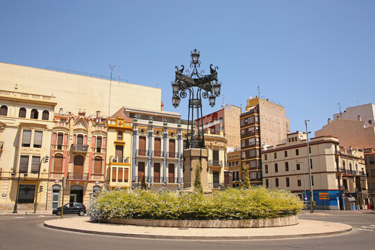 Group of historic modernist buildings a intricately designed street lamp called La Farola from 1929, city of Castellón, Valencia, Spain.
