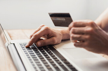 Man hand holding credit card and using laptop at home, Businessman or entrepreneur working, Online shopping, e-commerce, internet banking, spending money, working from home concept