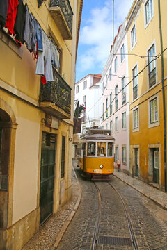 Historic yellow tram against old town streets, part of the tramway network since 1873, Lisbon, capital city of Portugal.