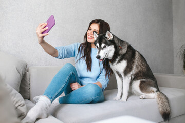 Happy young woman taking a selfie with husky dog at home
