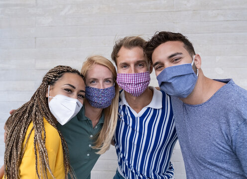 Portrait of happy young people smiling - Multiracial friends wearing protective face masks - Focus on the face of the blond northern woman