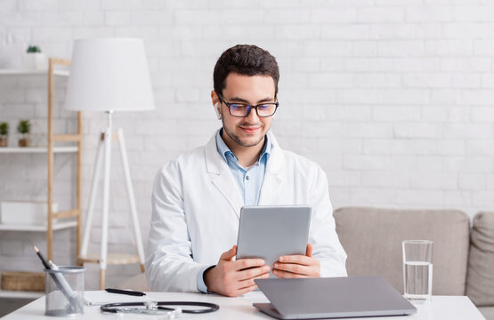 Doctor consultation online. Young man in glasses and white coat with wireless headphones looks at tablet