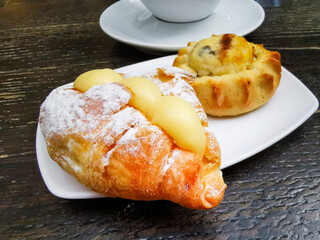 Fototapete - One small croissant with vanilla cream and cheese pastry with chocolate pieces served in white plate with black filtered coffee for a traditional greek breakfast